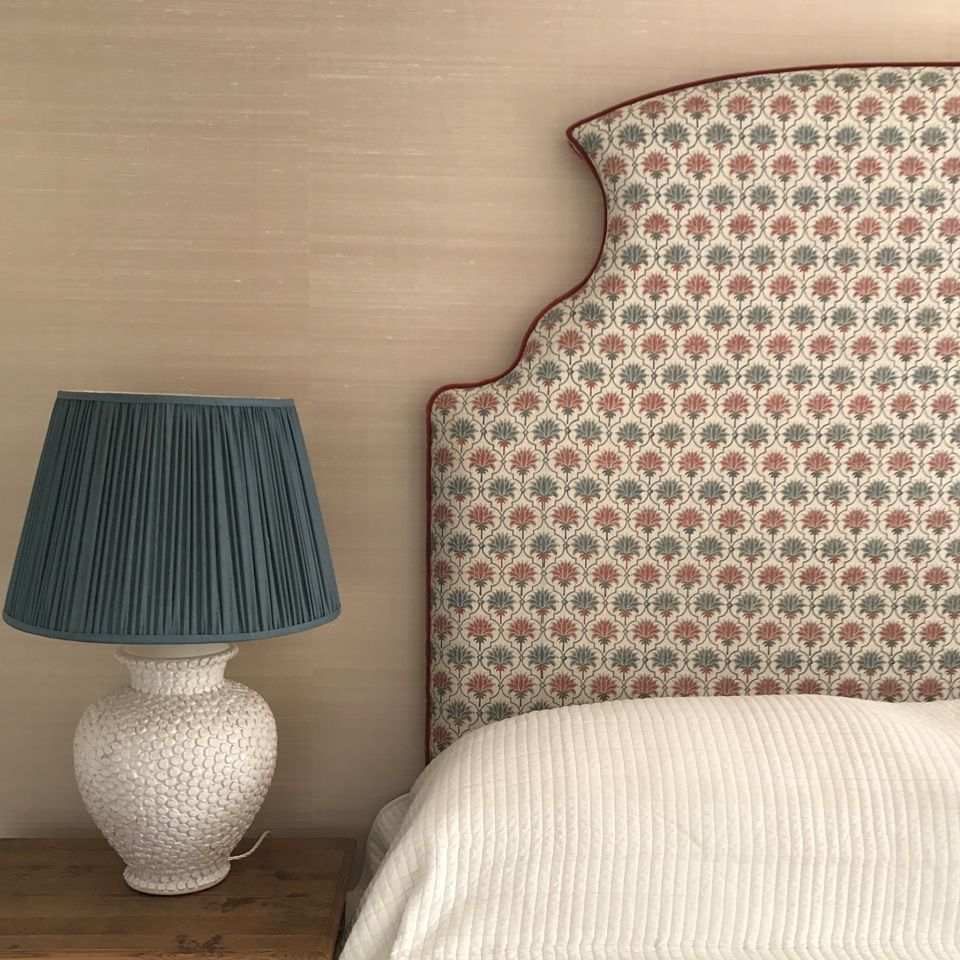 A bespoke headboard, stunning table lamp, and silk wallcovering